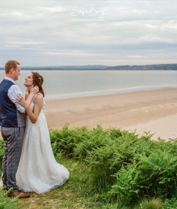 gower bridal hair styled bride standing on cliff with groom after gower wedding